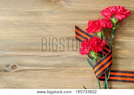 9 May card- red carnations and George ribbon lying on the wooden background with free space for text. 9 May still life. 9 May concept. Postcard of 9 May Victory day