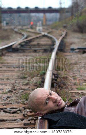 MOSCOW RUSSIA - APRIL 202004: Bald man lies head on rails near the railway station