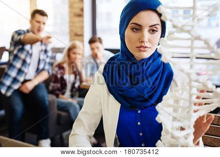 Do not pay attention. Pleasant attractive muslim student sdyting DNA model and getting ready for classes while her groupmates abusing her