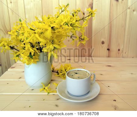 Coffee and bouquet of a Forsythia. The cup is filled with coffee. Forsythia is in a jug. Coffee and a bouquet are on a wooden table.