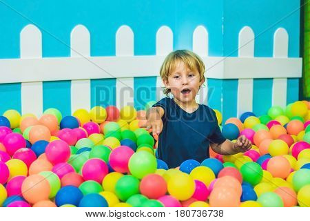 Happy Little Kid Boy Playing At Colorful Plastic Balls Playground High View. Funny Child Having Fun