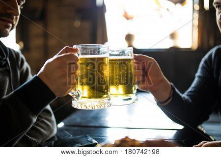 Close Up Of Male Hands Clinking Beer Glasses At Bar Or Pub