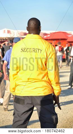 Black security guard wearing yellow jacket Concert