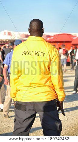 Black security guard wearing yellow jacket Concert