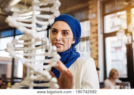 Interesting science. Pleasant cusrious muslim woman studying genetics and lookign at DNA model while expressing gladness