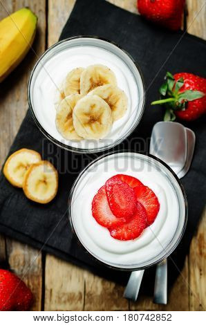 Greek yogurt strawberry and banana parfaits on a wood background.