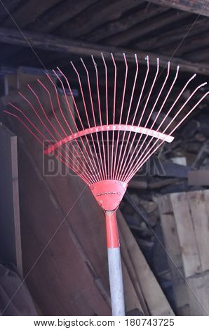 Red rake fan for cleaning in a shed at the cottage