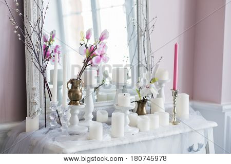 Shabby chic home design. Beautiful decoration table with a candles, flowers in front of a mirror.