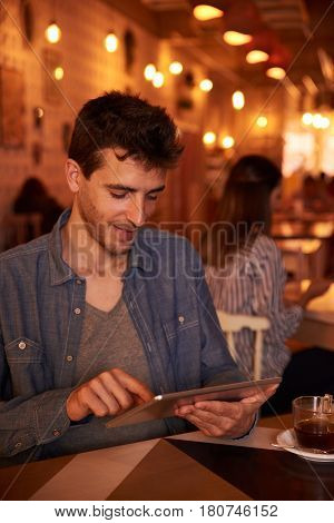 Smiling Young Man Typing On Tablet