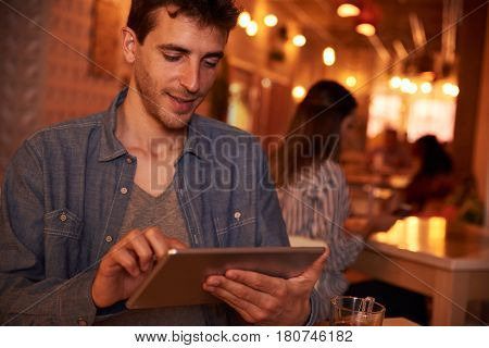 Smiling Young Millennial Texting In Restaurant
