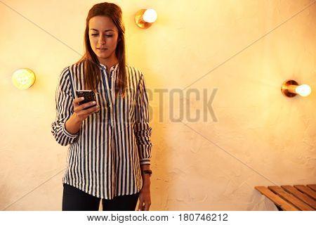 Pretty Millennial Standing Against A Wall