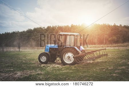 The Tractor Goes And Pulls A Plow Plowing A Field Before Landing Of Crops. In The Early Spring Morni