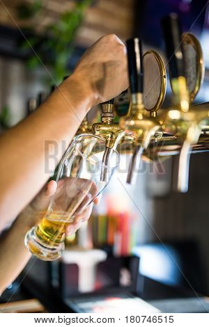 Mans Hand Pouring Pint Of Beer Behind The Bar In Pub