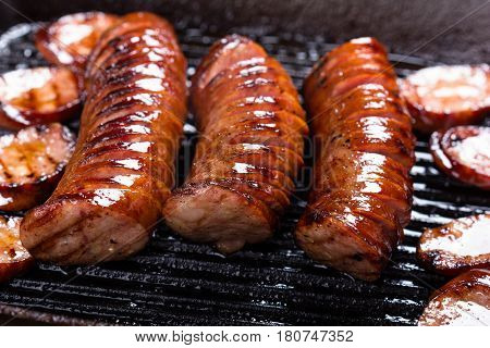 Polish traditional sausages fried on a cast iron skillet.