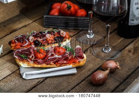 Tapas on crusty bread with red wine.