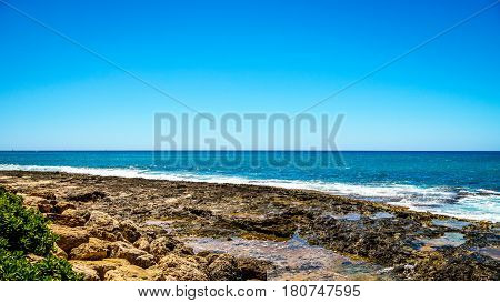 Waves of the Pacific Ocean crashing on the rocks on the shoreline of Ko Olina on the island of Oahu in the island state of Hawaii
