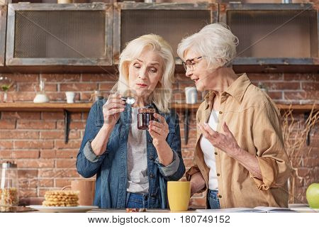 This jam is cooked by my recipe. Excited old woman is talking to her friend and smiling. Lady is tasting jam with enjoyment while standing in kitchen