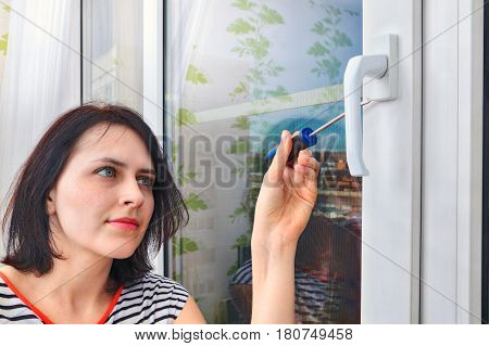 A young woman of 20 years old uninstalls the handle on the double-glazed window frame using a screwdriver.