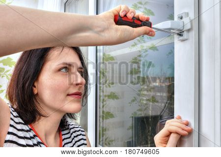 Young woman unscrews a window handle using screwdriver.