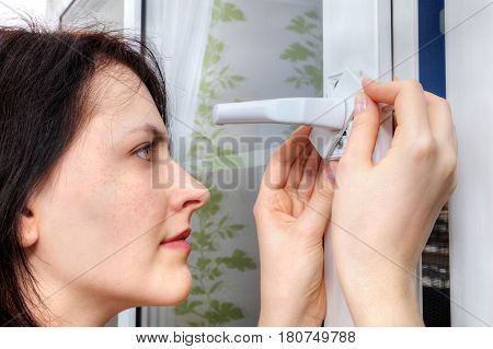 Young woman sets the limiter of opening the window on a plastic frame close-up.