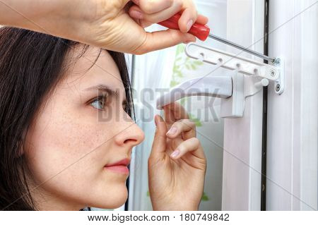 Young woman tightens the screw opening limiter plastic window using a screwdriver.