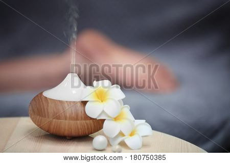Spa concept. Aroma oil diffuser on table against blurred background