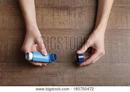 Female hands holding asthma inhaler on wooden background