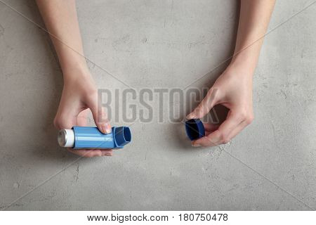 Female hands holding asthma inhaler on gray textured background