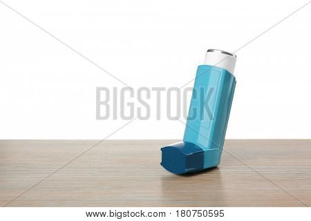 Asthma inhaler on wooden table