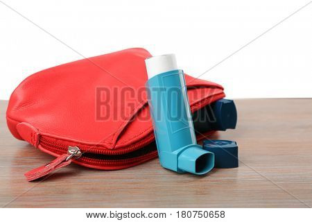 Cosmetic bag with asthma inhalers on wooden table