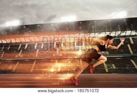 Athletic woman runs in a sport competition with lights trails on the stadium track