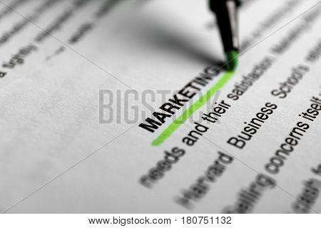 Underlining word MARKETING on paper sheet using felt pen, closeup