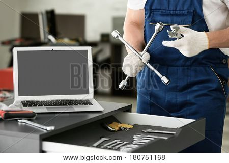 Auto mechanic with tools in car repair shop