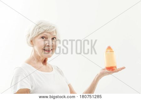 I am completely satisfied with this curative remedy. Portrait of excited old lady showing bottle of natural gel to camera. She is laughing. Isolated