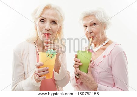 Carefree two old women are drinking cocktails from tubules. They are standing and looking at camera with joy. Isolated