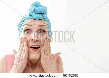 Mature lady is staring at camera with shock. She is touching her wrinkled face with sadness. Blue turban over her hair. Isolated and copy space in right side