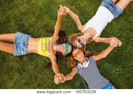 Top view of happy girls lying on grass and holding hands