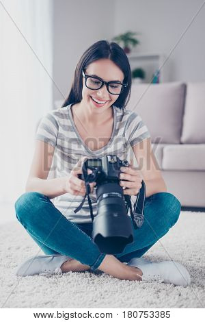 Young Pretty Brunette Photographer In Spectacles Looking At  Photos On A Digital Camera While Sittin