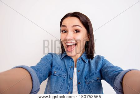 Portrait Of Excited Cheerful Smiling Young Pretty Woman  In Casual Jeans Shirt Making Selfie Photo