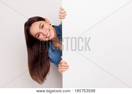 Young Smiling Long-haired Girl Standing And Appear  Near Big Poster,  Place For Copy Space
