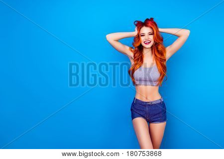 Excited Attractive Girl With Long Ginger Fair Hair Touch Head With Hands, Wearing In Short Jeans Sho