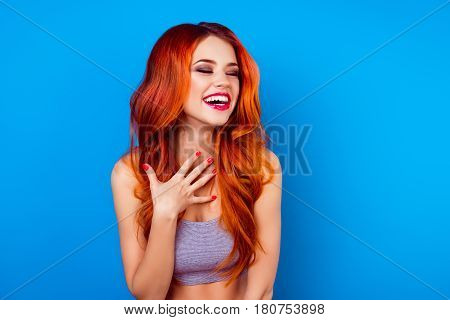 Portrait Of Cute Excited  Attractive Girl With Long Ginger Fair Hair Laughing While Standing On Blue