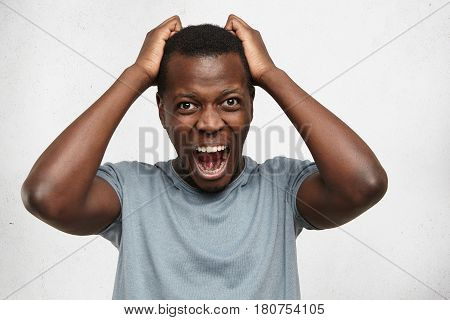 Portrait Of Desperate Annoyed Black Male Screaming In Rage And Anger Tearing His Hair Out While Feel