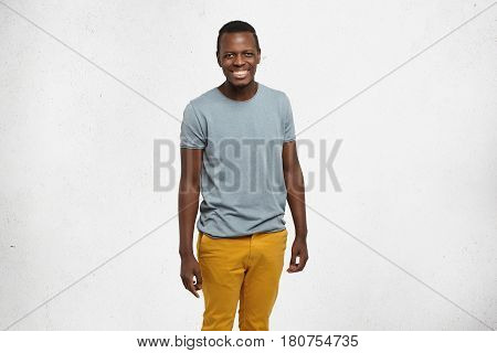 Studio Portrait Of Attractive Cheerful Young Dark-skinned Student In Grey T-shirt And Mustard Jeans
