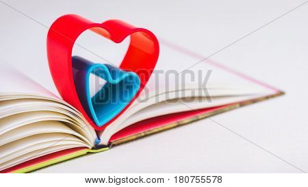Red and blue hearts over diary book on white table. Bright colours
