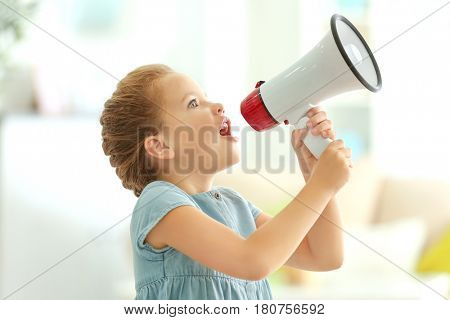 Cute little girl with megaphone at home