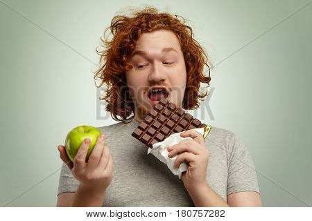 Headshot Of Fat Male With Ginger Hair Holding Big Bar Of Chocolate In One Hand And Green Apple In Ot