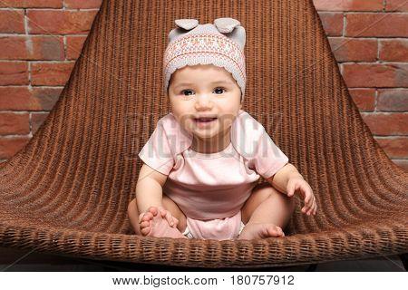 Cute little baby sitting in arm-chair near brick wall