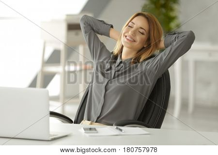 Beautiful young woman resting at workplace in office
