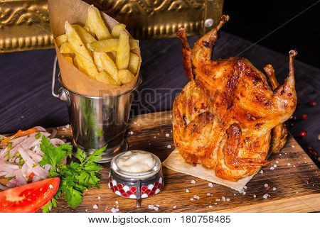 The carcasses of quails fried on coals are served with red pepper, onions salad and garlick sauce